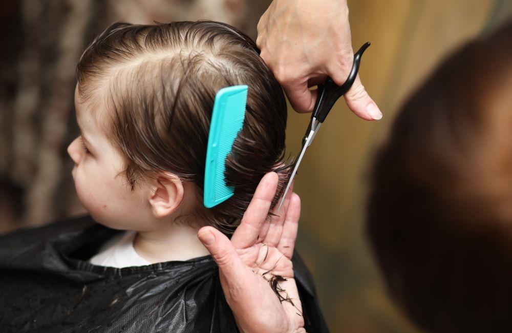 髪の毛をカットされている子供