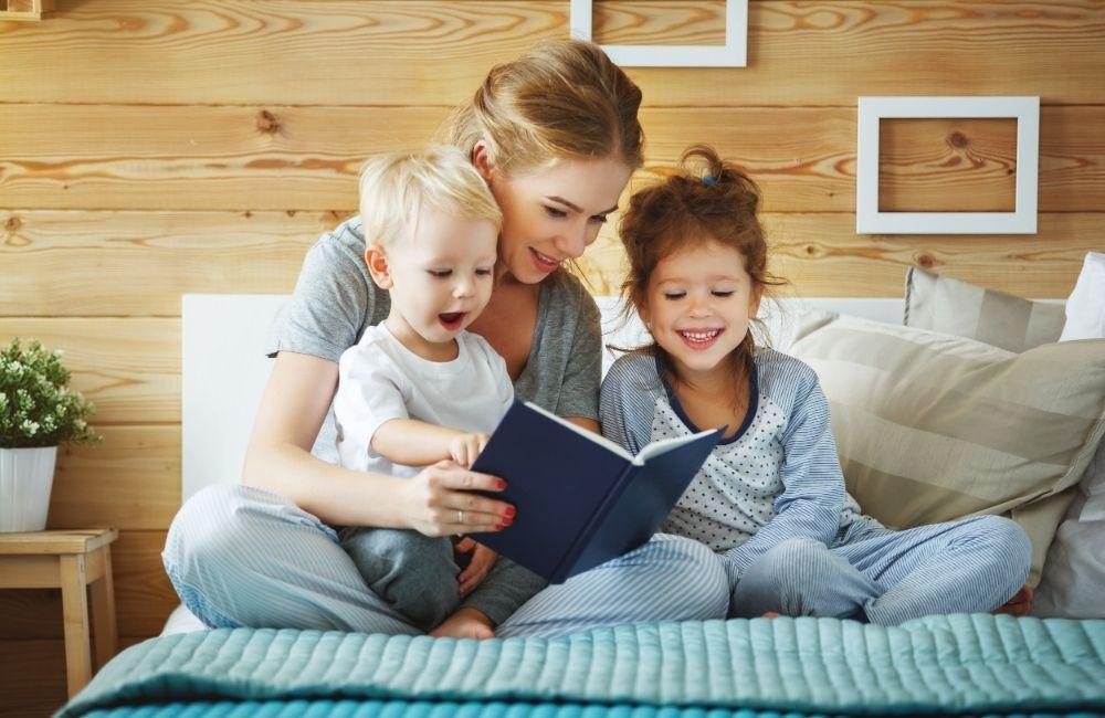 2人の子供に読み聞かせをする女性