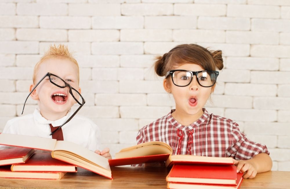 本を読み笑う2人の子供