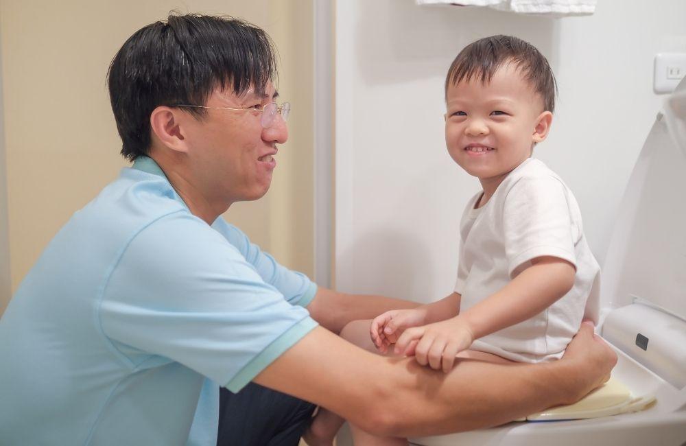 トイレトレーニングをする子供と見守る父親