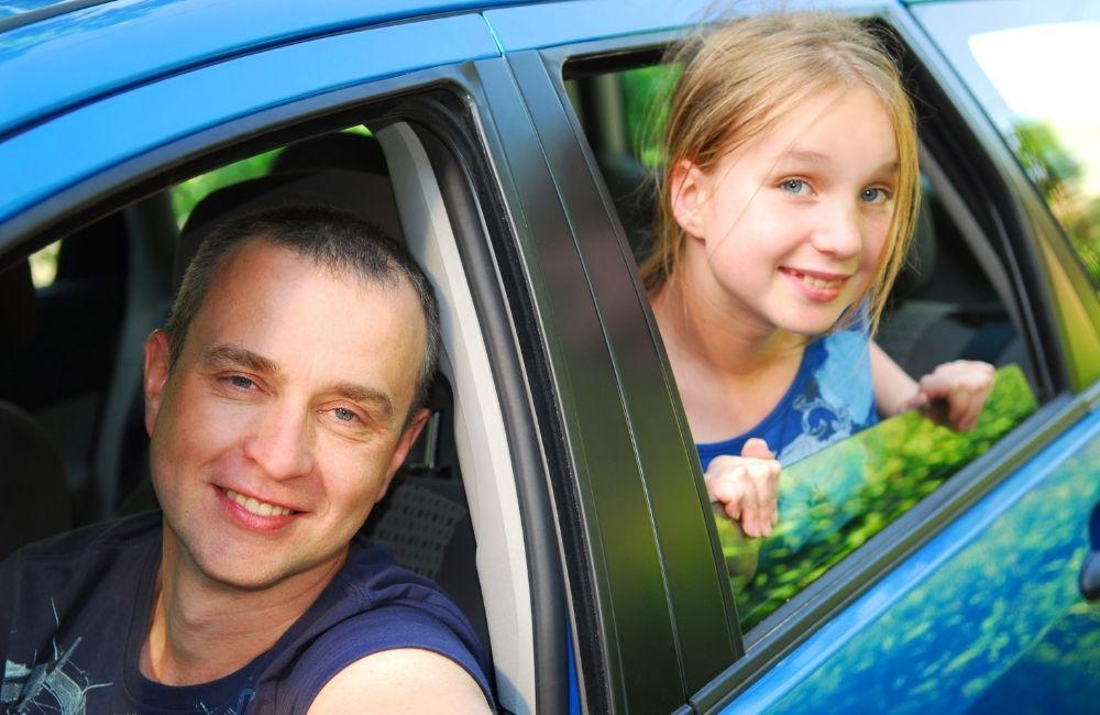 車の窓から顔を出す女の子と親